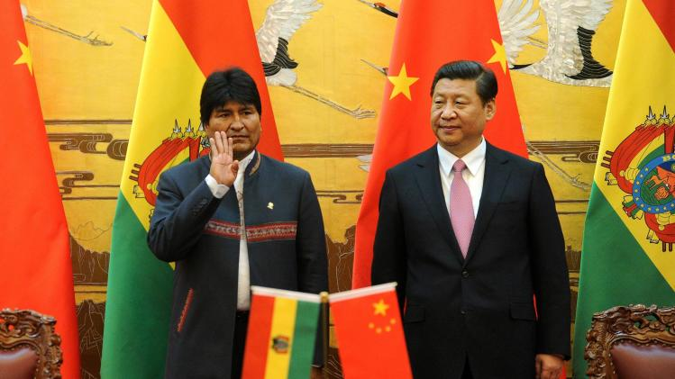 Bolivia's President Evo Morales gestures next to Chinese President Xi Jinping during a signing ceremony at the Great Hall of the People in Beijing