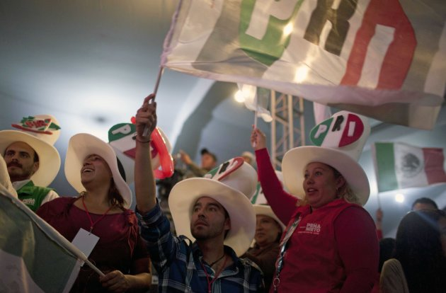 Supporters of Enrique Pena Nieto, presidential candidate for the Revolutionary Institutional Party (PRI) gather at party headquarters as exit polls begin to come in for general elections in Mexico City, Mexico, Sunday, July 1, 2012. Pena Nieto is leading Mexico's elections with about 40 percent of the vote, exit polls showed Sunday, signaling a return of his long-ruling party to power after a 12-year hiatus. (AP Photo/Alexandre Meneghini)