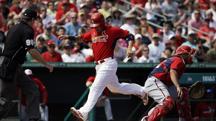 St. Louis Cardinals' Yadier Molina, center, scores off a single by teammate Mark Ellis in the second inning of an exhibition spring training baseball game against the Washington Nationals, Saturday, March 8, 2014, in Jupiter, Fla