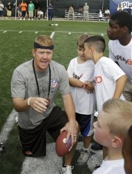 Cleveland Browns quarterback rookie Brandon Weeden huddles with kids taking part in an NFL football Play 60 youth clinic at the Cleveland Browns training facility in Berea, Ohio Friday, June 29, 2012. (AP Photo/Mark Duncan)