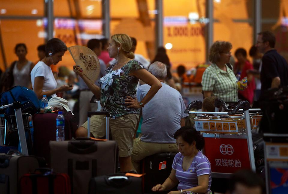 A tourist fans herself as she stranded with others at the Beijing Capital International Airport after flights are canceled due to the heavy rains in Beijing, China Saturday, July 21, 2012. Heavy downpour flooded roads and caused hundreds of flights to be canceled in the capital. (AP Photo) CHINA OUT
