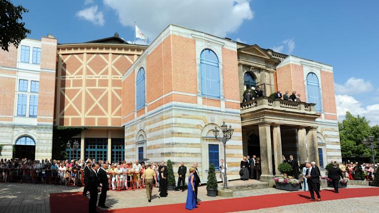 "Guests arrive for opening of the Bayreuth Festival in Bayreuth, Germany, Friday, July 25, 2014. The annual Richard-Wagner opera festival is one of the most important cultural a events in Germany. Bayreuth's annual opera festival has gotten off to an unexpectedly dramatic start, with a technical malfunction forcing an interruption shortly after the opening performance of Richard Wagner's ""Tannhaeuser"" kicked off.German news agency dpa, citing its reporters at the performance, reported that the audience was asked to leave the auditorium after about 20 minutes for safety reasons. (AP Photo/dpa,Tobias Hase)"