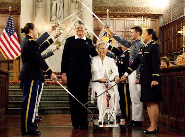 Brenda Sue Fulton, center left, and Penelope Gnesin, proceed through an honor guard forming an arch of raised swords after exchanging wedding vows at the U.S. Military Academy at West Point, N.Y. Saturday, Dec. 1, 2012.