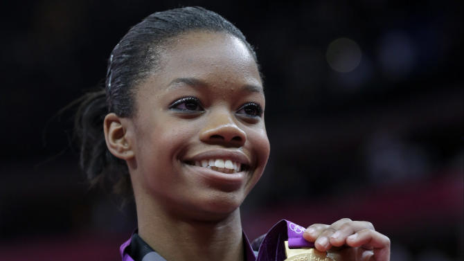 FILE - In this Aug. 2, 2012 file photo, U.S. gymnast Gabrielle Douglas displays her gold medal during the artistic gymnastics women's individual all-around competition at the 2012 Summer Olympics in London. Douglas is back in the gym.The Olympic all-around champion was to practice Monday afternoon, May 20, 2013 after meeting with coach Liang Chow to discuss her comeback plan. The workout is in her old gym in West Des Moines, Iowa.  (AP Photo/Julie Jacobson, File)