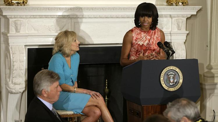 First lady Michelle Obama, right, accompanied by Jill Biden, addresses the National Governors Association, Monday, Feb. 25, 2013, in the State Dining Room of the White House in Washington. (AP Photo/Charles Dharapak)