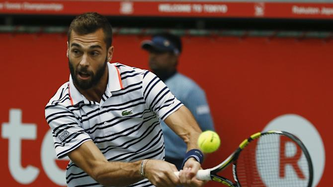 Paire returns the ball to Nishikori during their men's singles semi-final tennis match at the Japan Open championships in Tokyo