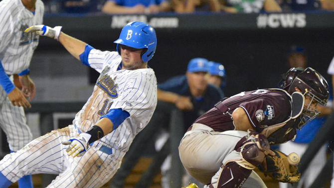 UCLA's Cody Regis, left, slides safely to home plate on a single by Eric Filia ahead of the throw to Mississippi State catcher Nick Ammirati in the sixth inning of Game 2 in their NCAA College World Series baseball finals, Tuesday, June 25, 2013, in Omaha, Neb. (AP Photo/Ted Kirk)