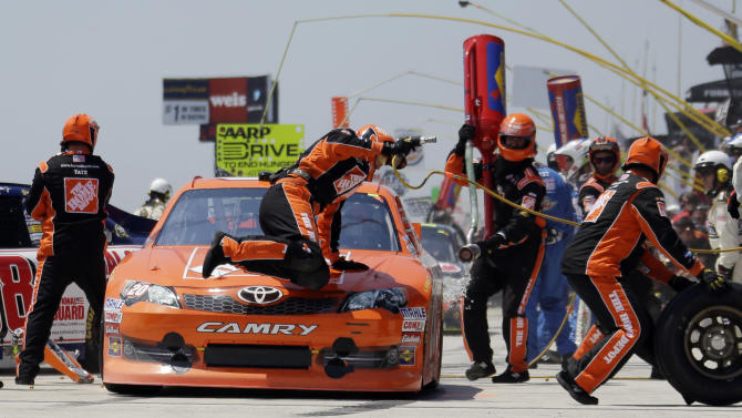 A crew member slides across the hood of Joey Logano's car during a pit stop in the NASCAR Sprint Cup auto race, Sunday, June 10, 2012, in Long Pond, Pa. (AP Photo/Matt Slocum)