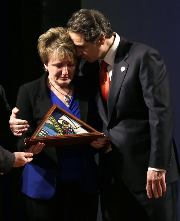 New York Gov. Andrew Cuomo embraces Janina Kaczowka, mother of slain West Webster firefighter Tomasz Kaczowka, after presenting her with a state flag during his third State of the State address at the