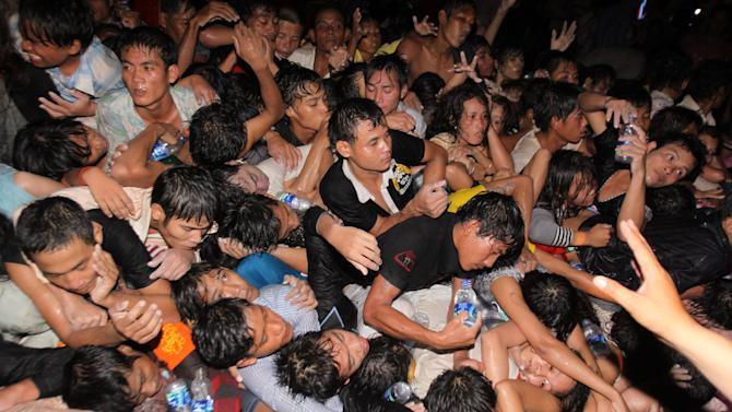 A crowd of Cambodians are pushed onto a bridge on the last day of celebrations of a water festival in Phnom Penh, Cambodia, Monday, Nov. 22, 2010. Thousands of people celebrating a water festival on a small island in a Cambodian river stampeded Monday evening, killing at least 17 people, a hospital official said. Hundreds more were hurt as the crowd panicked and pushed over a bridge to the mainland. (AP Photo/Heng Sinith)