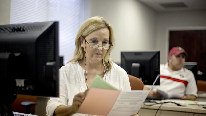 FILE- In this Aug. 22, 2012 file photo, Judy Smith, of Dalton, Ga., looks over paperwork as she files for unemployment for the first time since being laid off from a catering job at a convention center in Dalton, Ga. Fewer Americans applied for unemployment benefits last week, and a private survey showed businesses stepped up hiring in August. The data sketched a brighter outlook for the job market one day before the government reports on August employment. (AP Photo/David Goldman, File)