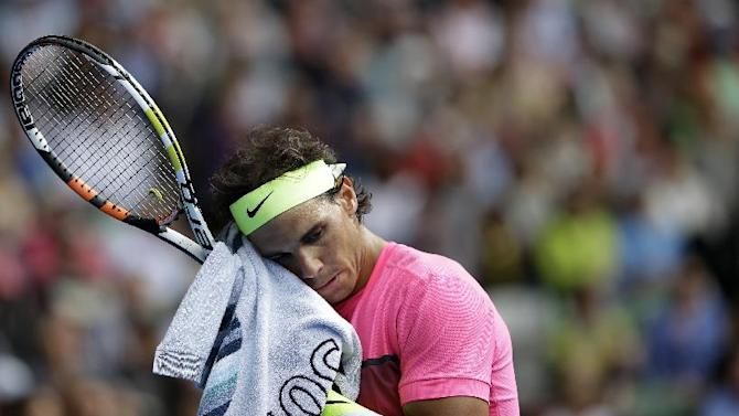 Rafael Nadal of Spain wipes the sweat from the face as he plays Tomas Berdych of the Czech Republic during their quarterfinal match at the Australian Open tennis championship in Melbourne, Australia, Tuesday, Jan. 27, 2015