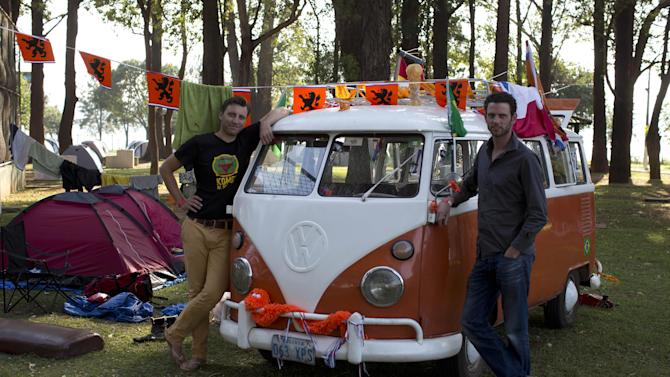 Laurens Kraal, left and Udo Van Heteren stand next to their Kombi van after driving from Bolivia to Brazil at the Oranjecamping site during the 2014 soccer World Cup in Sao Paulo, Brazil, Sunday, June 22, 2014. The group of seven Dutch men arrived at Sao Paulo after a 13-day journey from Bolivia in the orange hippie van that dates back to at least 45 years. (AP Photo/Dario Lopez-Mills)