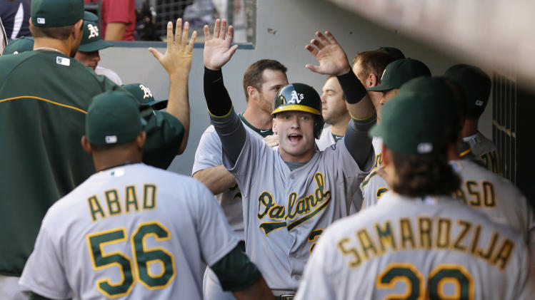 Oakland Athletics' Josh Donaldson, center, is greeted in the dugout after he scored against the Seattle Mariners in the first inning of a baseball game, Friday, July 11, 2014, in Seattle. (AP Photo/Ted S. Warren)