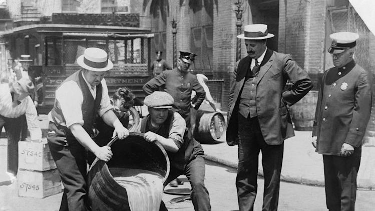 "New York City Deputy Police Commissioner John A. Leach, right, watching agents pour liquor into sewer following a raid, ca. 1921. After the Mullan-Gage Act was repealed in 1923, New York police were no longer bound to enforce Prohibition as seen on ""Prohibition."""