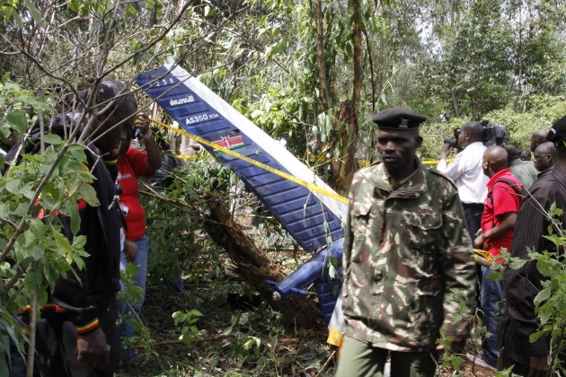 Kenyan officials inspect the area of the helicopter wreckage after it crashed in Ngong Forest, on the outskirts of Nairobi, Kenya, Sunday, June 10, 2012. Kenyan police say Sunday that cabinet minister George Saitoti, who once served as Kenya's vice president, was one of seven people killed in a helicopter crash on the outskirts of Nairobi. (AP Photo/Khalil Senosi)