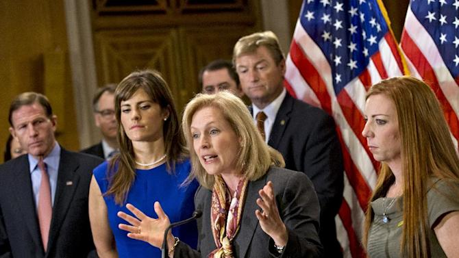 Sen. Kirsten Gillibrand, D-N.Y., is flanked by Sarah Plummer, left, a Marine Corps veteran and victim of sexual assault, and Kate Weber, right, a veteran who was sexually assaulted during her service in the Army, during a news conference on Capitol Hill in Washington, Tuesday, Nov. 19, 2013. They are surrounded by supporters of her proposal to let military prosecutors rather than commanders make decisions on whether to prosecute sexual assaults in the armed forces. At far left is Sen. Richard Blumenthal, D-Conn. Sen. Dean Heller, R-Nev., stands behind Sen. Gillibrand at center. (AP Photo/J. Scott Applewhite)