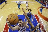 Philadelphia 76ers&#39; Spencer Hawes (00) shoots as New Orleans Hornets&#39; Anthony Davis, bottom right, defends and Robin Lopez (15) watches) during the first half of an NBA basketball game, Tuesday, Jan. 15, 2013, in Philadelphia. (AP Photo/Matt Slocum)
