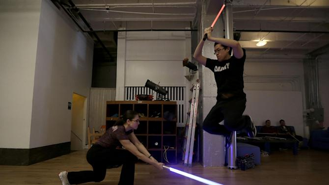 Student Aaron Cheng jumps over a light saber swung by fellow student Starshine Medeiros during a Golden Gate Knights class in San Francisco, Sunday, Feb. 10, 2013. A group of San Francisco Star Wars fans who want to travel to a galaxy not that far away have created a combat choreography class for Jedis-in-training with their weapon of choice: the light saber. (AP Photo/Jeff Chiu)