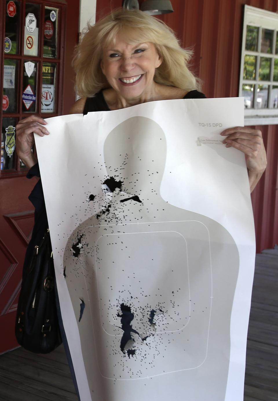 In this Sunday, May 19, 2013, photo, Sandra Keller shows off her target filled with shotgun holes as she leaves a shooting range in Houston. Keller lives in the first residential area being trained and equipped by a nonprofit that is giving away free shotguns to single women and neighborhoods with high crime rates. (AP Photo/Pat Sullivan)