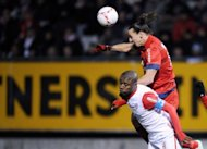 Paris Saint-Germain's forward Zlatan Ibrahimovic (Top) fights for the ball with Nancy's defender Andre Luiz during their French L1 football match at Marcel Picot Stadium in Tomblaine