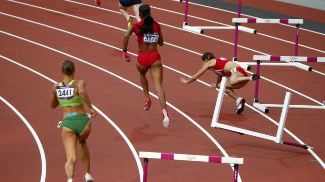 Bulgaria's Vania Stambolova crashes into a hurdle as Lithuania's Egle Staisiunaite and T'Erea Brown of the U.S. run in the women's 400m hurdles round 1 heat during the London 2012 Olympic Games at the Olympic Stadium