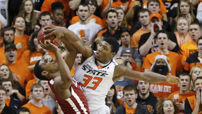 Oklahoma State guard Marcus Smart (33) blocks a three-point shot attempt by Oklahoma guard Steven Pledger (2) with 18 seconds to go in overtime of an NCAA college basketball game in Stillwater, Okla., Saturday, Feb. 16, 2013. Oklahoma State won 84-79. (AP Photo/Sue Ogrocki)
