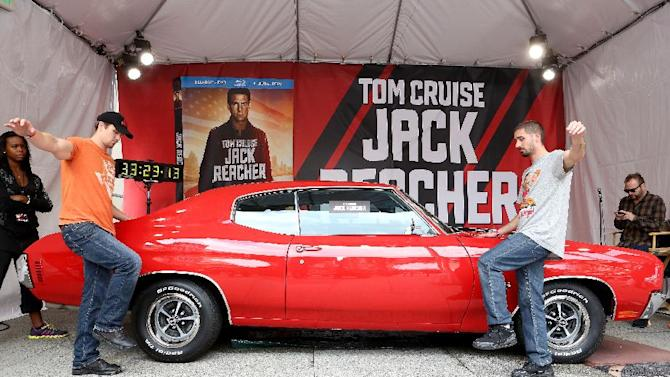 IMAGE DISTRIBUTED FOR  PARAMOUNT HOME MEDIA DISTRIBUTION - The final contestants struggle to keep their hands on a classic 1971 Chevelle SS, like the one featured in the action-packed film JACK REACHER, during the thirty-fourth hour of a grueling competition to win the car held at the Hollywood & Highland Center on Tues., May 7, 2013 in Los Angeles. The competition celebrates the debut of JACK REACHER on Blu-ray, DVD and Digital Download today. (Photo by Casey Rodgers/Invision for Paramount Home Media Distribution/AP Images)