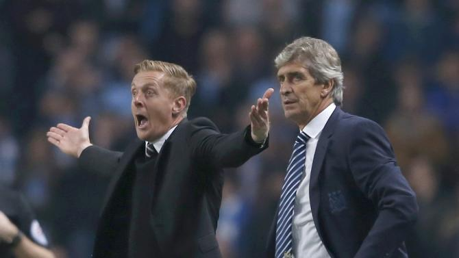 Manchester City manager Manuel Pellegrini and Swansea City manager Garry Monk react during their English Premier League soccer match at the Etihad stadium in Manchester