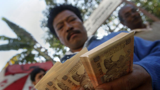 An Indian counts currency notes in front of the Reserve Bank of India in Gauhati, India, Tuesday, Nov. 22, 2011. The Indian rupee plunged to an all time low against the dollar Tuesday as global demand for dollars and India's darkening economic picture swamped out central bank efforts to staunch the decline. (AP Photo/Anupam Nath)