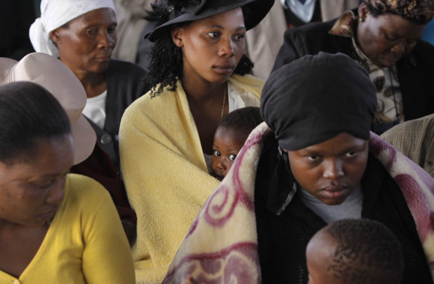 Mourners attend a memorial service at the Lonmin Platinum Mine near Rustenburg, South Africa, Thursday, Aug. 23, 2012 after police shot and killed 34 striking miners and wounded 78 last week. Demands