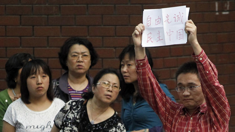"""A Chinese man holds up a sign which reads """"Freedom Guangcheng, Democracy China"""" at a hospital where blind Chinese legal activist Chen Guangcheng is believed to be seeking treatment in Beijing, China, Wednesday, May 2, 2012.  Chen who sparked a diplomatic tussle by holing up in the U.S. Embassy in Beijing for six days emerged Wednesday after U.S. officials said China had assured his safety. (AP Photo/Ng Han Guan)"""