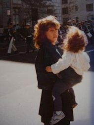 My mom carrying me at a parade in NYC, around 1985
