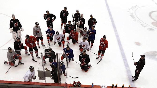 Members of the New Jersey Devils gather during NHL hockey training camp, Friday, Sept. 19, 2014, in Newark, N.J. (AP Photo/Julio Cortez)