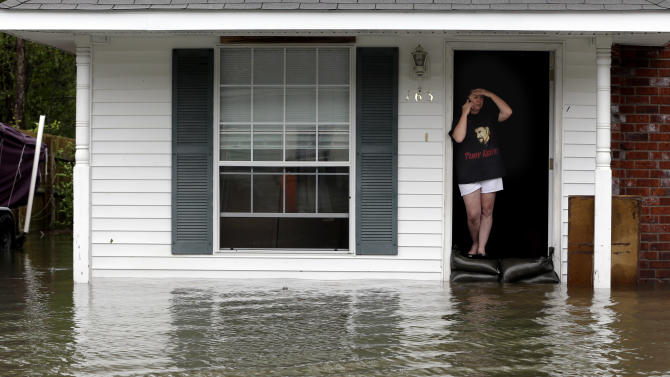 A resident whose home is surrounded by flood waters talks on the phone, Thursday, Aug. 30, 2012, in LaPlace, La. Isaac has caused major flooding in the region. (AP Photo/Eric Gay)