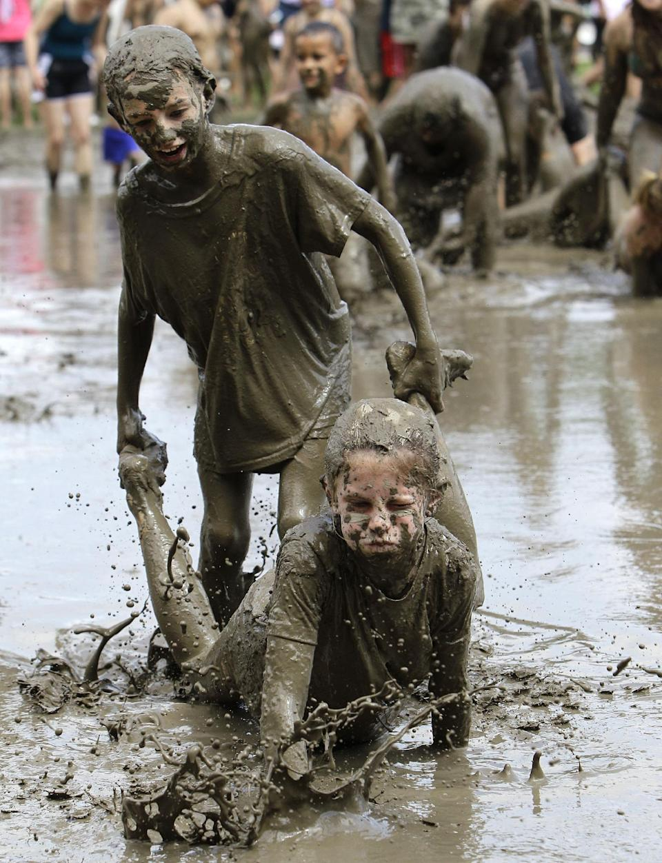 Stephanie Strong, 9, standing, helps Grace Lipscomb, 10, both of Howell, wheel barrow in the mud in Westland, Mich., Tuesday, July 9, 2013. Hundreds of kids enjoyed the annual Mud Day event in a 7-by-150-foot mud pit. (AP Photo/Paul Sancya)
