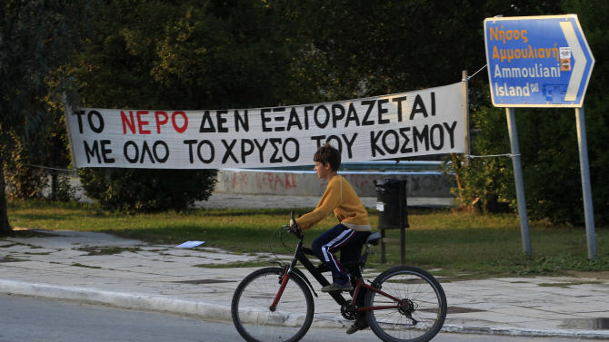 """In this Thursday, Oct. 11, 2012, a boy cycles past a banner which reads in Greek """" All the gold in the world can't buy water"""" at the village of Ierissos in the Halkidiki peninsula in northern Greece. Mining company Hellas Gold expect s the mine to be up and running by mid 2015 creating about 2000 jobs for the next five years. But while some see the gold mine seen as a savior _ as Greece enters a sixth year of recession amid record-high unemployment _ others revile it as an environmental catastrophe that will do little to help the economy.  (AP Photo/Nikolas Giakoumidis)"""
