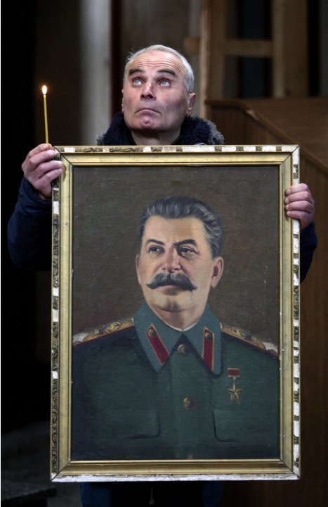 A Georgian holds a portrait of former Soviet dictator Joseph Stalin and a candle marking the 60th anniversary of his death as he stands in a church in Stalin's home town of Gori, some 80 km (50 miles)