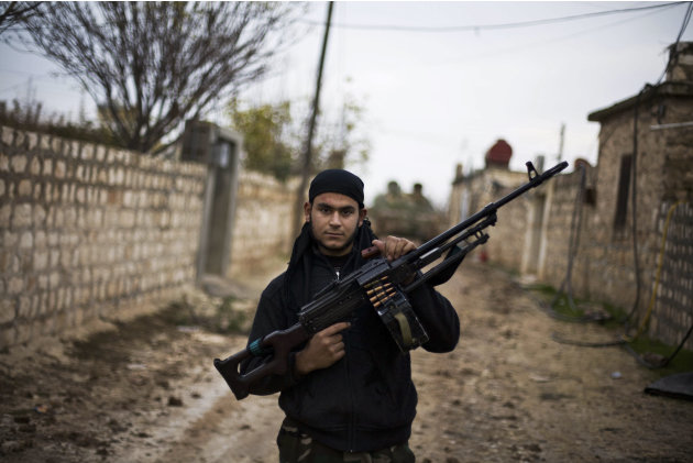 In this Wednesday, Dec. 12, 2012 photo, a Free Syrian Army fighter poses as he carries his weapon in the northern province of Aleppo, Syria. Syria's civil war has killed more than 40,000 people. (AP P