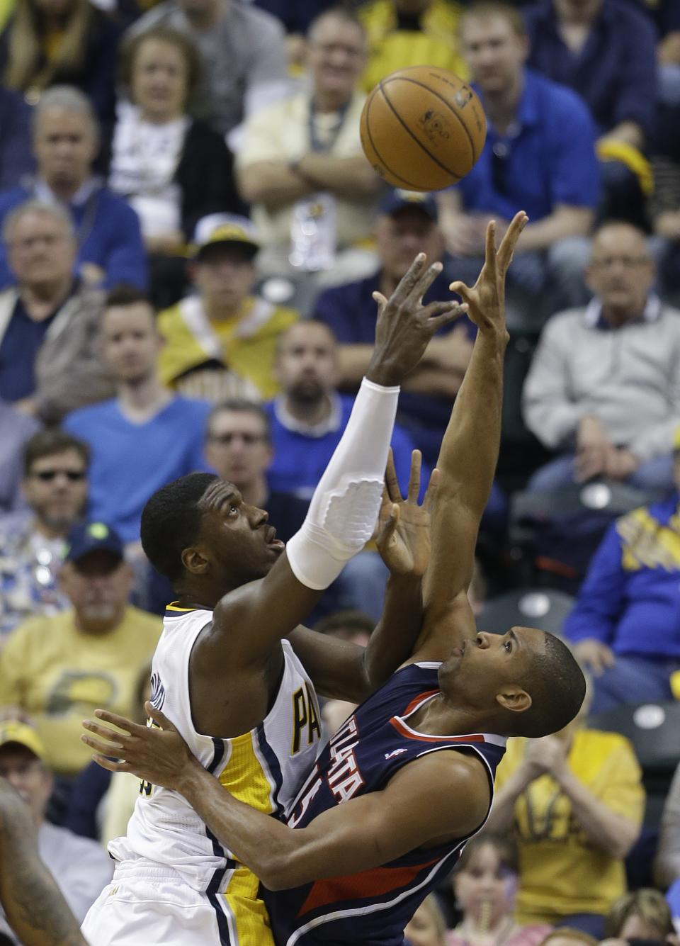 Indiana Pacers' Roy Hibbert, lefts, shoots against Atlanta Hawks' Al Horford during the first half of Game 1 in the first round of the NBA basketball playoffs on Sunday, April 21, 2013, in Indianapolis. (AP Photo/Darron Cummings)