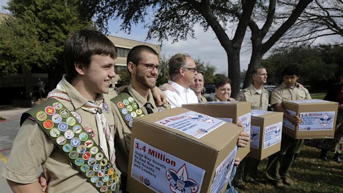 FILE - In this Feb. 4, 2013 file photo, James Oliver, left, hugs his brother and fellow Eagle Scout, Will Oliver, who is gay, as Will and other supporters carry four boxes filled with a petition to end the ban on gay scouts and leaders in front of the Boy Scouts of America headquarters in Dallas, Texas. Under pressure over its long-standing ban on gays, the Boys Scouts of America is proposing to lift the ban for youth members but continue to exclude gays as adult leaders. The Scouts announced Friday, April 19, 2013 that the proposal would be submitted to the roughly 1,400 voting members of its National Council at a meeting in Texas the week of May 20, 2013. (AP Photo/Tony Gutierrez, File)