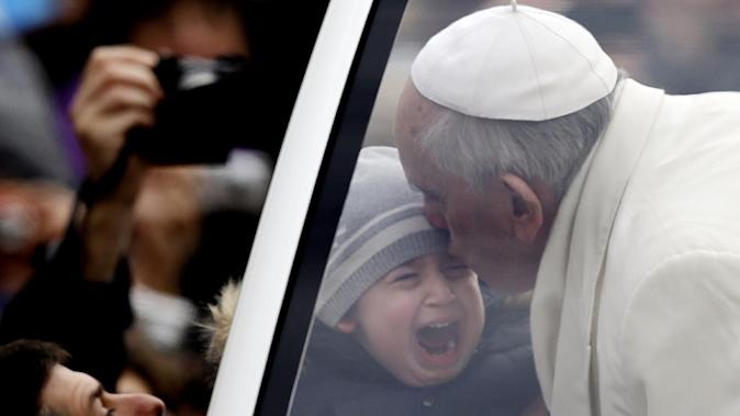 Pope Francis kisses a crying child during his tour through the crowd in St. Peter's Square, part of his weekly general audience at the Vatican, Wednesday, Jan. 29, 2014. (AP Photo/Gregorio Borgia)