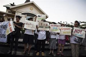 People hold placards as they take part in an anti-violence campaign in central Bangkok