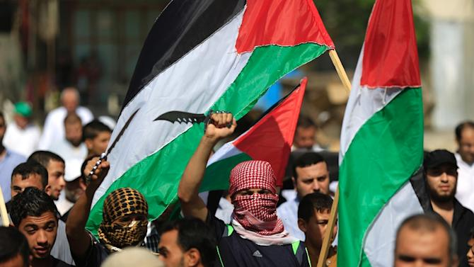 Palestinian protesters carry knives and the national flag during a demonstration in the Jabalia refugee camp, in northern Gaza on October 16, 2015