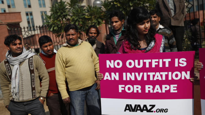 Indian men watch as a woman protests outside the court where the accused in a gang rape of a 23-year-old woman are to be tried, in New Delhi, India, Monday, Jan. 21, 2013. Legal proceedings in the fatal gang-rape attack on a student in India's capital were set to begin Monday in a fast-track court for crimes against women that has stirred debate over how best to deliver justice to rape victims. (AP Photo/Saurabh Das)
