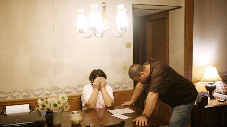 FILE - In this March 25, 2009 file photo, Allison Kimble holds her head in her hands while she and her husband Scott read over a school application for their daughter in Perry County, Tenn. Both parents have lost their auto-related jobs. In small communities like Perry County, the loss of auto plant supplier jobs has pushed unemployment to a Depression-level 25.4 percent, the fourth-highest rate among U.S. counties in March. (AP Photo/Josh Anderson)