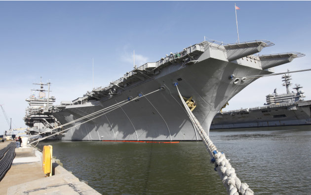 In this March 8, 2012 photo, the nuclear powered aircraft carrier USS Enterprise sits at the pier as sailors move supplies and equipment in preparation for the ships final deployment of the at the Nor