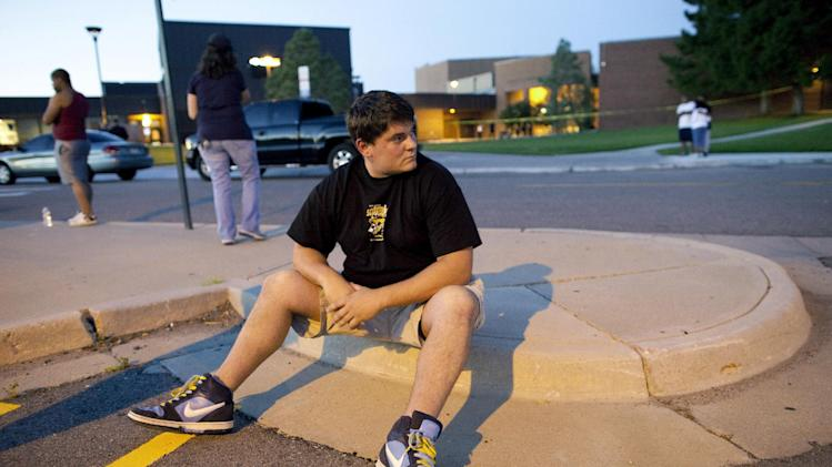 """Eyewitness Chandler Brannon, 25, sits outside Gateway High School where witnesses were brought for questioning after a shooting at a movie theater showing the Batman movie """"The Dark Knight Rises,"""" Friday, July 20, 2012 in Aurora.  A gunman wearing a gas mask set off an unknown gas and fired into the crowded movie theater killing 12 people and injuring at least 50 others, authorities said. (AP Photo/Barry Gutierrez)"""