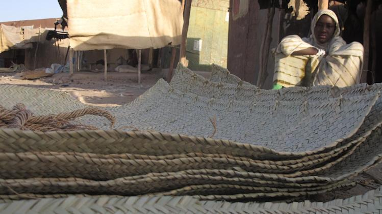 In this Wednesday, Feb. 20, 2013 photo, a young vendor waits for clients alongside woven reed mats of the type purchased by fleeing Islamists, apparently to camouflage their vehicles, in Timbuktu, Mali. An instruction on camouflaging cars is one of 22 tips on how to avoid drones, listed on a document left behind by the Islamic extremists as they fled northern Mali from a French military intervention in January. The tip sheet, found Feb. 6 by an AP reporter in Timbuktu, reflects how al-Qaida's chapter in North Africa anticipated a military intervention that would make use of drones, as the battleground in the war on terror worldwide is shifting from boots on the ground to unmanned planes in the air.(AP Photo/Rukmini Callimachi)