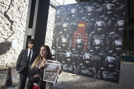 A woman poses for a photo in front of a new art installation by British graffiti artist Banksy in New York